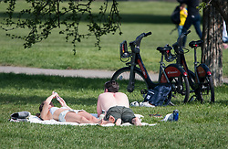 © Licensed to London News Pictures. 11/04/2020. London, UK. A couple sunbathing on Primrose Hill, London on Easter Bank holiday weekend, during a pandemic outbreak of the Coronavirus COVID-19 disease. The public have been told they can only leave their homes when absolutely essential, in an attempt to fight the spread of coronavirus COVID-19 disease. Photo credit: Ben Cawthra/LNP