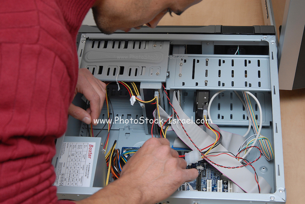 Male computer technician working on the inner parts of a PC