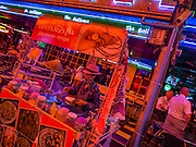 20 SEPTEMBER 2013 - BANGKOK, THAILAND:  A crepe vendor waits for customers on Soi Cowboy in Bangkok. Soi Cowboy is one of the notorious Entertainment Districts in Bangkok. Entertainment District has emerged as euphemism for red light district. Prostitution is officially illegal in Thailand but it is widely condoned. For western men, Soi Cowboy, along with Soi Nana and Patpong are among the most well known entertainment districts in Bangkok.      PHOTO BY JACK KURTZ