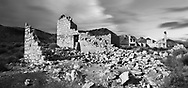 Crumbling buildings at the Rhyolite Ghost Town are slowly melting back into the desert from which they long ago sprang, Rhyolite Nevada, An Abandoned Town Near Death Valley, USA