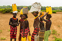 Dassanach tribe girls carrying water containers, Omo Valley, Ethiopia.