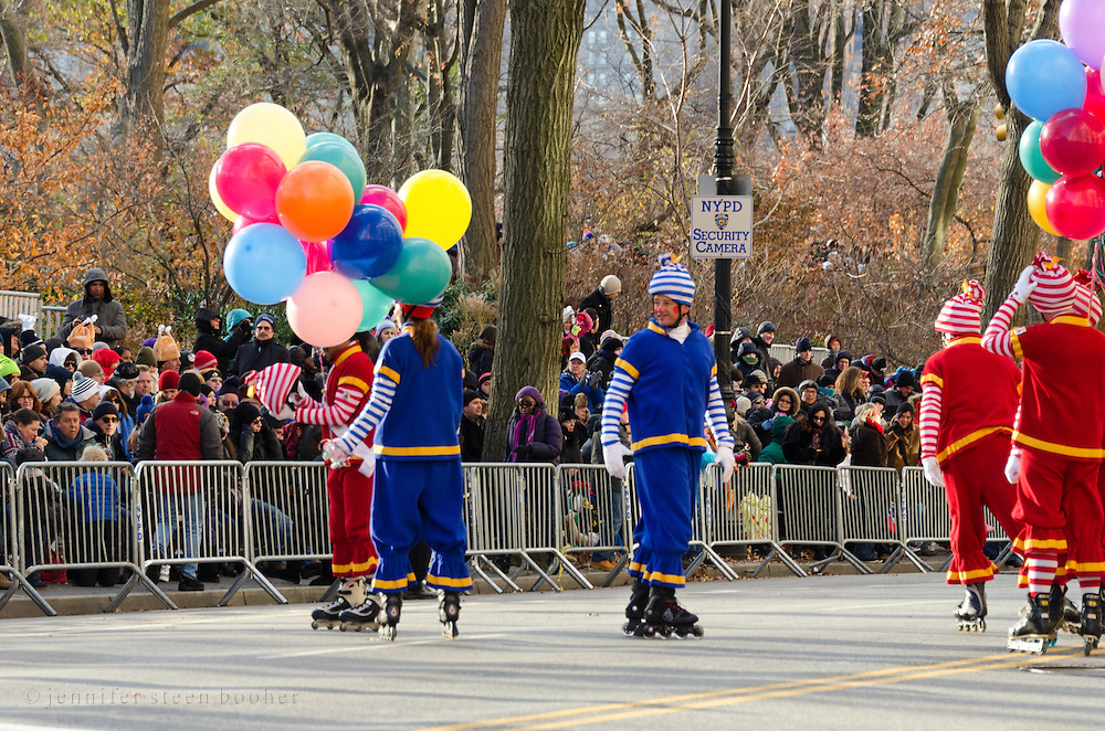 Rollerskating clowns perform for crowds waiting for the Macy's Thanksgiving Day Parade to start.