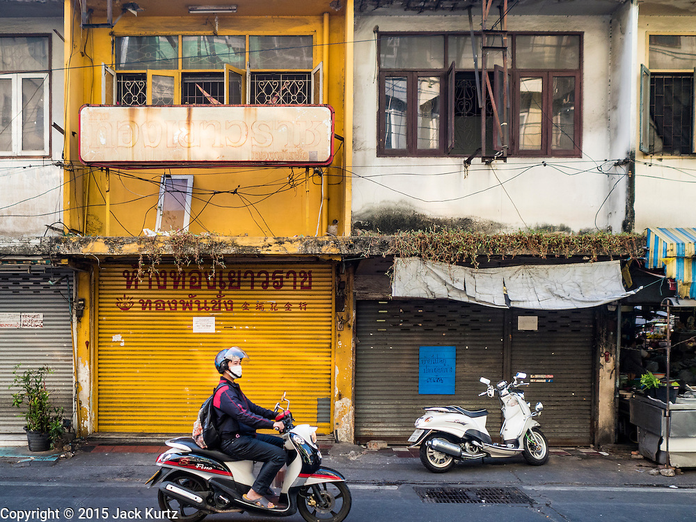 30 DECEMBER 2015 - BANGKOK, THAILAND:   A man drives his motorcycle past condemned buildings in front of Bang Chak Market. The market is supposed to close permanently on Dec 31, 2015. The Bang Chak Market serves the community around Sois 91-97 on Sukhumvit Road in the Bangkok suburbs. About half of the market has been torn down. Bangkok city authorities put up notices in late November that the market would be closed by January 1, 2016 and redevelopment would start shortly after that. Market vendors said condominiums are being built on the land.           PHOTO BY JACK KURTZ
