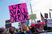 January, 21st, 2017 - Paris, Ile-de-France, France: Women protesters with 'We shall overcome' placard at Trocadero with Eiffel Tower behind. Thousands of protesters in Paris join anti-Trump Women's March around the world.