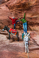 Bedouin boys playing on their donkeys in the Siq, the mile long narrow gorge that leads into the Petra Archaeological Park, Petra, Jordan.