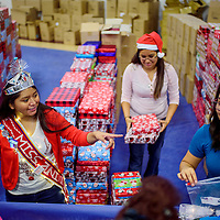 Tasha Yamautewa, left, Tiffany Nahohai and Brittny Seowtewa hand out gifts from large piles of wrapped parcels during the Toys for Tots event at the Zuni Wellness Center in Zuni Thursday.