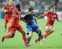 Lionel Messi of Argentina, center, challenges Christian Kwesi Annan, left, and Kwok Kin-pong of Hong Kong during a friendly football match in Hong Kong, China, 14 October 2014.<br /> <br /> Lionel Messi needed just six minutes to make his mark in Argentina's 7-0 rout of Hong Kong in a friendly at Hong Kong Stadium on Tuesday (14 October 2014). The Barcelona star Messi scored twice after going on as a substitute for the last 30 minutes of the game to celebrate the 100th anniversary of the Hong Kong Football Association. Napoli striker Gonzalo Higuain and Benfica's Nicolas Gaitan also scored two goals each after Sevilla's Ever Banega had opened scoring in the 19th minute.