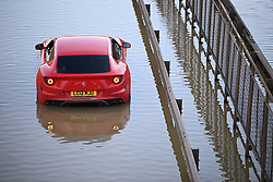 © Licensed to London News Pictures. 06/07/2020. London, UK. A Ferrari sports car stuck in severe flooding on the North Circular road at Brent Cross in North London where passengers have been rescued from vehicles and cars are stranded. Photo credit: Ben Cawthra/LNP
