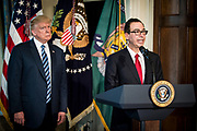 President Donald Trump looks on as Treasury Secretary Steven Mnuchin delivers remarks before Trump was to sign one executive order and two presidential memoranda on tax and Wall Street regulations in Washington, District of Columbia, U.S., on Friday, April 21, 2017. This was President Trump's first visit to the Treasury Department.