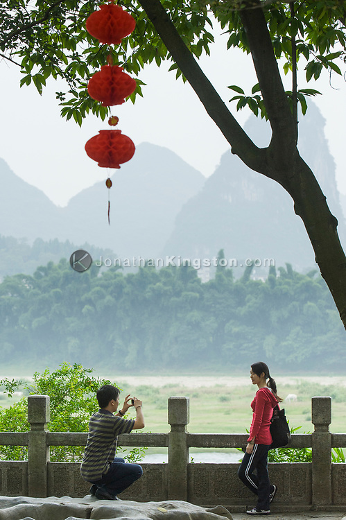 A tourist gets her picture taken above the Li River in Yangshuo, China.