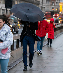© Licensed to London News Pictures. 13/01/2020. London, UK. Commuters brave the wind and rain on Waterloo Bridge as London braces for high winds and heavy squally rain during this evening's rush hour. Storm Brendan is forecast to blow in towards the South East with winds expected to peak up to 45mph. Photo credit: Alex Lentati/LNP
