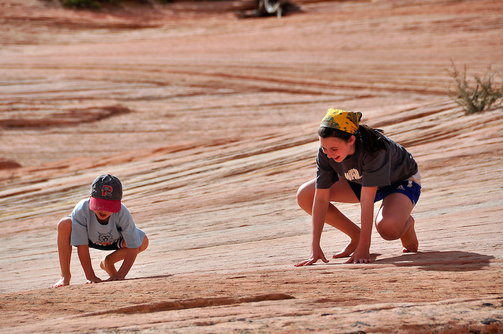 Children playing on sandstone in Zion National Park, Utah.