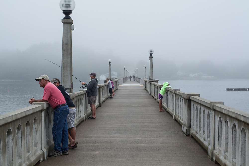 People fishing on the footbridge across the Passagassawakeag River in Belfast, Maine.