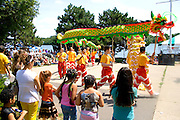 Asian dragon pole dancers perform ceremony before attentive audience. Dragon Festival Lake Phalen Park St Paul Minnesota USA