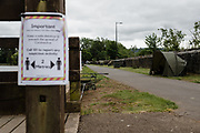 MERTHYR TYDFIL, Wales - 04 JUNE 2020 - A sign explaining to social distance while a fisher has his rods and tent set up.
