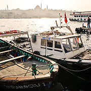 Fishing boats moorred next to the Karakoy Fish Market in Istanbul near the Galata Bridge. In the distance is the Suleymaniye Mosque.