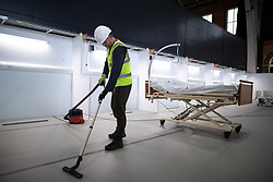 © Licensed to London News Pictures. 12/04/2020. Manchester, UK. Cleaner WAYNE HUMPHREYS (39) vacuum cleaning one of the wards . The National Health Service is building a 648 bed field hospital for the treatment of Covid-19 patients , at the historical railway station terminus which now forms the main hall of the Manchester Central Convention Centre . The facility is due to open on Easter Monday , 13th April 2020 , and will treat patients from across the North West of England , providing them with general medical care and oxygen therapy after discharge from Intensive Care Units . Photo credit: Joel Goodman/LNP