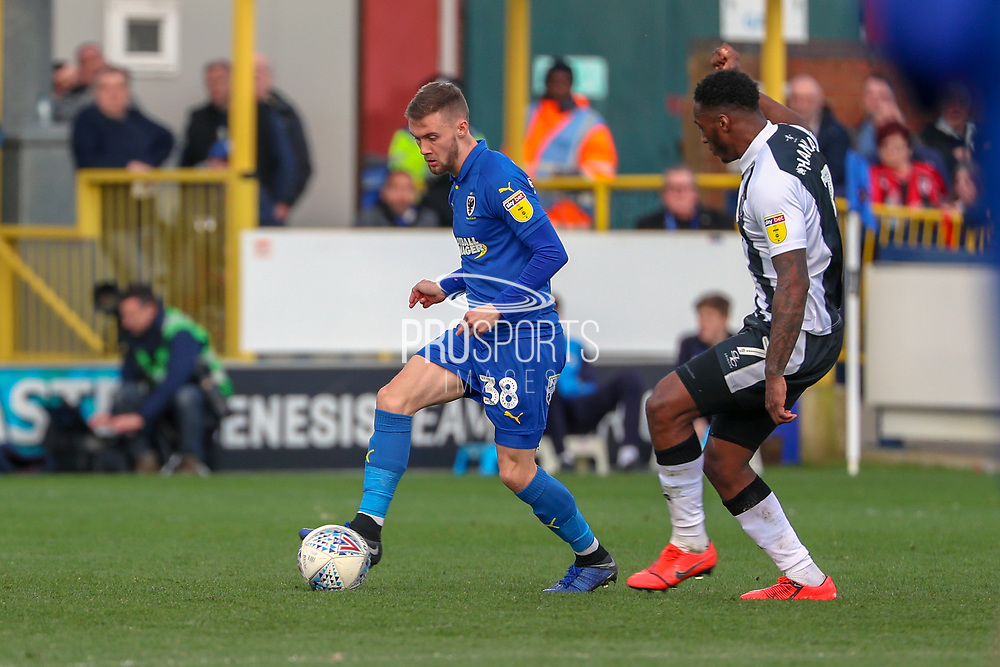 AFC Wimbledon attacker Shane McLoughlin (38) taking on Gillingham attacker Brandon Hanlan (7) during the EFL Sky Bet League 1 match between AFC Wimbledon and Gillingham at the Cherry Red Records Stadium, Kingston, England on 23 March 2019.