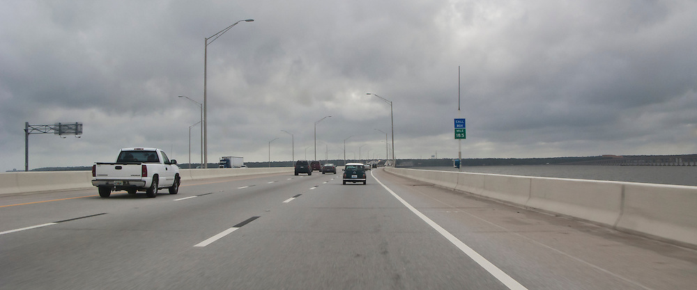 crossing Escambia Bay in western Florida on Interstate 10 with a railroad bridge and coal fired power plant in the distance with a sky filled with stormy cumuluonimbus clouds filling the sky.
