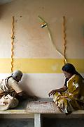 Two elders play a board game outside their cottage in the Tamaraikulum Elders village, Tamil Nadu, India