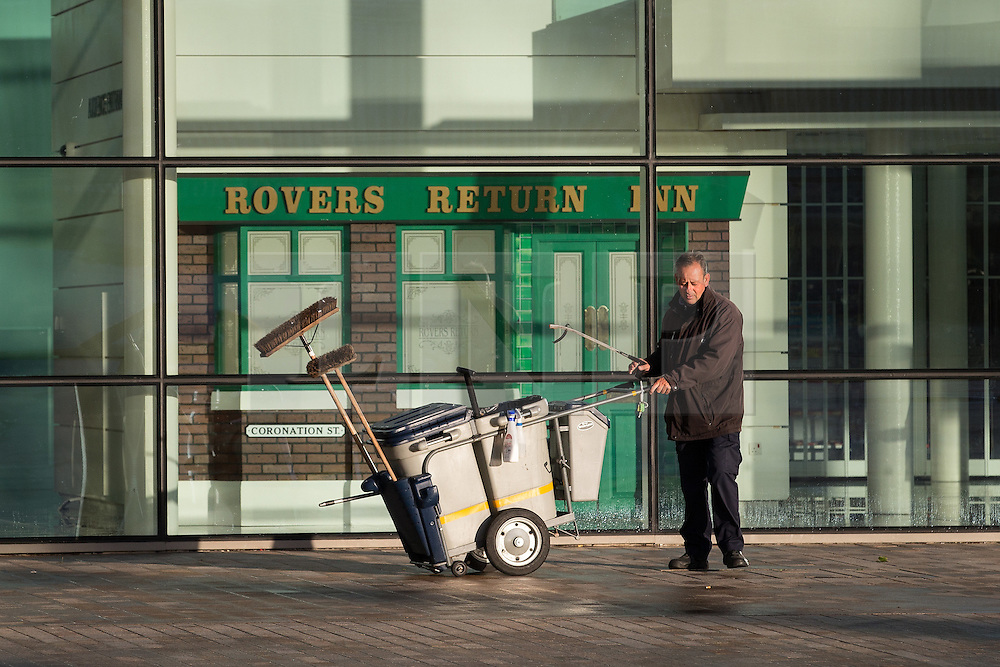 © Licensed to London News Pictures . 24/09/2014 . Media City , Salford , UK . A road cleaner picks up rubbish outside a mock up of the Rovers Return Inn . Autumn sunshine and big reflected light off the surface of glass buildings at Salford's Media City this morning as commuters travel to work  . Photo credit : Joel Goodman/LNP