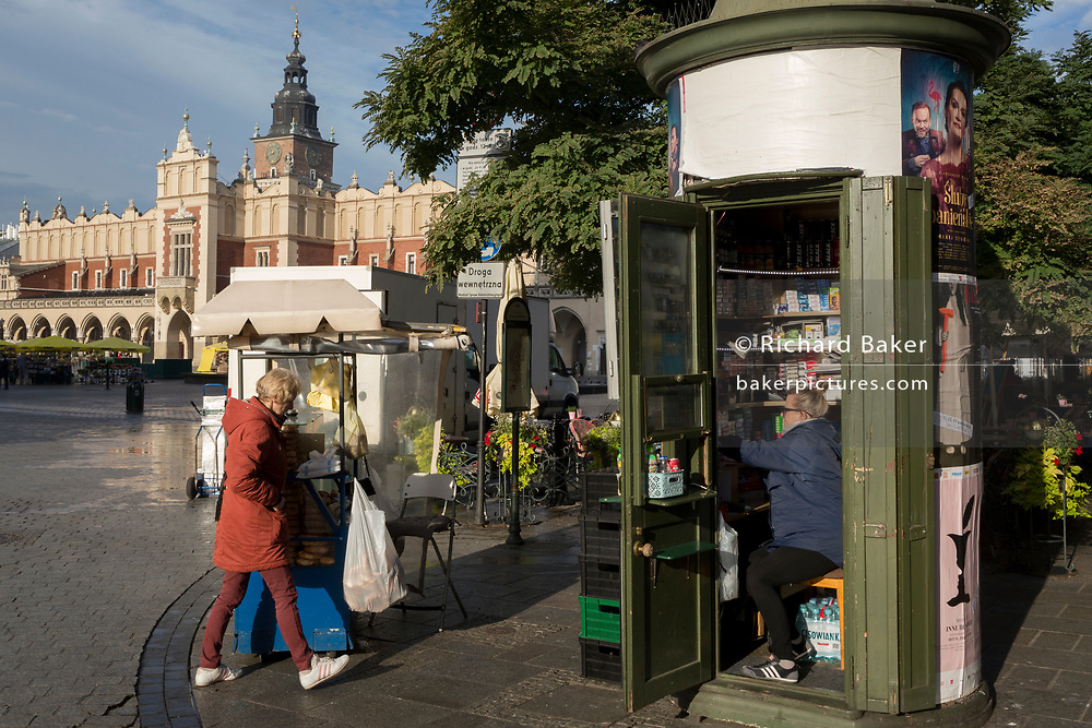 Opposite the Renaissance Cloth Hall, a 'tabac' lady and a snack seller open for business on Rynek Glowny market square, on 23rd September 2019, in Krakow, Malopolska, Poland.