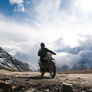 Scene from a group of motorcycle riders riding Royal Enfield bikes on a tour from Manali to Spiti in HImachal Pradesh Kunzum pass (4590 m) is the gateway to Spiti from Kulu & Lahaul.