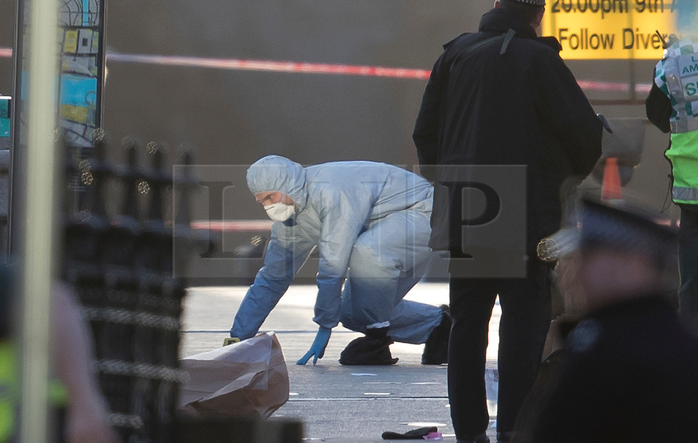 © Licensed to London News Pictures.22/03/2017.London, UK. A forensics officer examines the pavement on Westminster Bridge after a terrorist attack on the Houses of Parliament in Westminster, London.Photo credit: Peter Macdiarmid/LNP