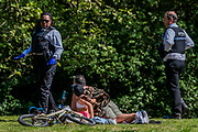 Parks police ask people to move on - Battersea Park is reasonably busy,  and generally people maintain some social distance, as the sun is out and it is warmer. The 'lockdown' continues for the Coronavirus (Covid 19) outbreak in London.