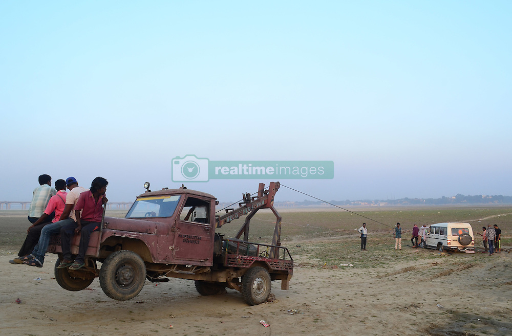 October 17, 2016 - Allahabad, India - Indian people sit on a crane to balance weight as they pull a vehicle, strucked in mud , on the banks of Holy Sangam, confluence of three great Rivers ,Ganges,Yamuna and mythical Saraswati, in Allahabad on October 17,2016. (Credit Image: © Ritesh Shukla/NurPhoto via ZUMA Press)