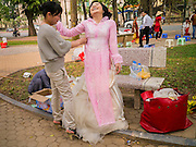 02 APRIL 2012 - HANOI, VIETNAM:  Couples gather for photos in a park in Hanoi, the capital of Vietnam. Their photographers bring several sets of clothes, from formal wear to traditional Vietnamese attire, and the couples have their pictures made in different poses in parks in the neighborhood.     PHOTO BY JACK KURTZ