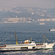 An old passenger ferry on the Bosphorus Strait in Istanbul's busy shipping lanes with the city of Istanbul in the background.