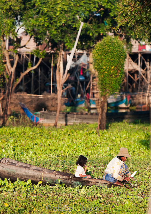 A woman cutting plants from her boat in the floating village of Kompong Phluk on the great Tonlé Sap lake, Cambodia