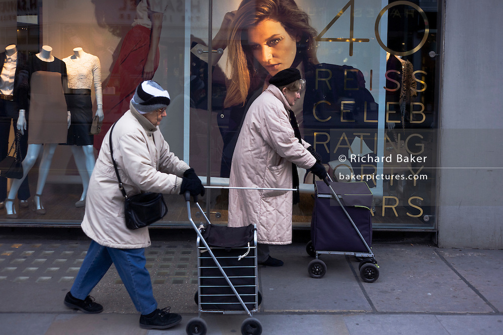 Two elderly ladies pushing trolleys walk past a young womens' clothes shop in Chelsea.