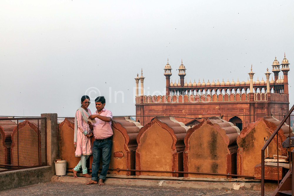 A couple on the roof of the Jama Masjid in Old Delhi look at a mobile telephone. The Masjid-i Jahan-Numa World-reflecting Mosque, commonly known as the Jama Masjid, is one of the largest mosques in India. It was built by Mughal Emperor Shah Jahan between 1644 and 1656.