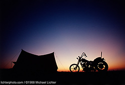 """Home on the Range. Sturgis, SD. 1988<br /> <br /> Limited Edition Print from an edition of 50. Photo ©1988 Michael Lichter.<br /> <br /> The Story: A bike, a tent, and the open plains.  You and the elements.  Motorcycling teases us with the freedom to be on the road, stop when and where you want to, and slow down and experience the world first hand.  Janice Joplin comes to mind; """"Freedom's just another name when you've got nothing left to lose""""."""
