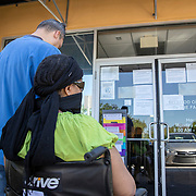 Recipients of the Access food stamp program read the signs that are taped to the doors explaining the temporary closure of the building on Friday, April 3, 2020 in Orlando, Florida. (Alex Menendez via AP)