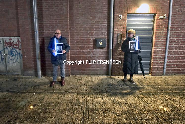 Nederland, Nijmegen, 21-2-2019 In Nijmegen werd het vergissingsbombardement van 75 jaar geleden in 1944 herdacht. Langs de zgnd. brandgrens van de binnenstad stonden tientallen koren en musici die tussen 20.00 uur en 20.15 uur het muziek brachten. Ook bij de honderden met kaarsjes verlichte naamplaatjes die in de straten ingelegd zijn stonden verwanten met soms een foto van hun omgekomen familielid. Foto: Flip Franssen