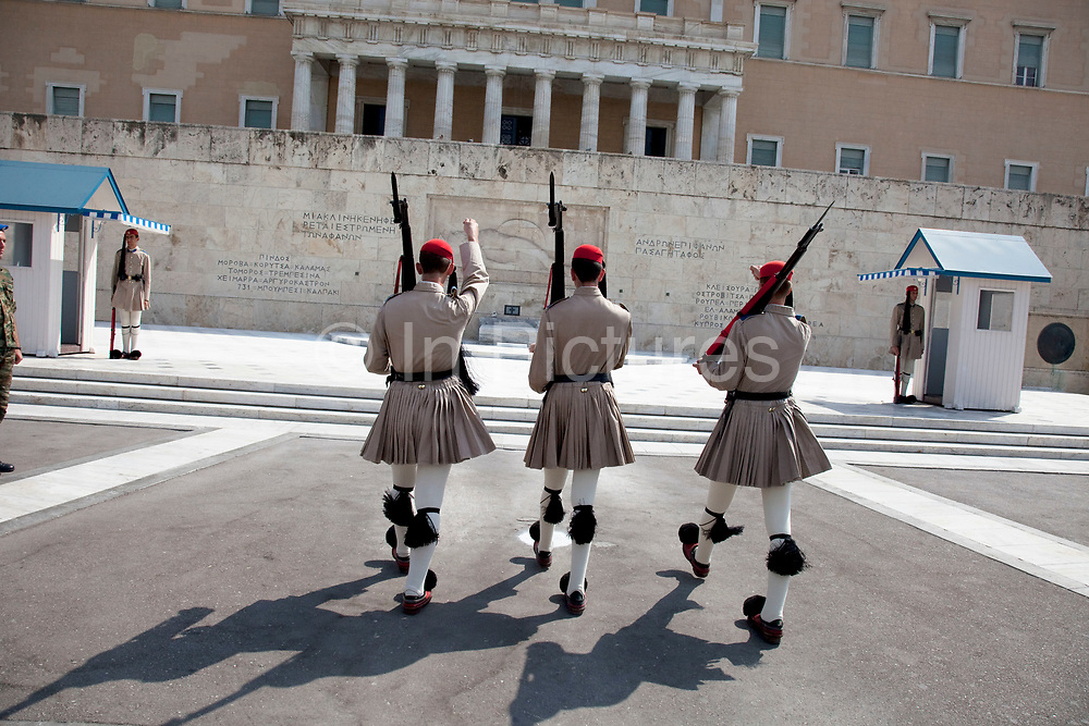 """Changing the Guard (often incorrectly referred to as the Changing of the Guard), refers to a formal ceremony in which sentries providing ceremonial guard duties at important institutions are relieved by a new batch of sentries. The ceremonies are often elaborate and precisely choreographed. In the state capital, Athens, members of the elite Evzones light infantry unit, provide a 24-hour honor guard, with an hourly guard change, at the Presidential Mansion and at the Tomb of the Unknown Soldier, off Syntagma Square at the foot of the Hellenic Parliament. The Changing the Guard at the Tomb of the Unknown Soldier in particular has become a tourist attraction, with many people marvelling at the guards, who stand motionless for two 20-minute intervals, during their 1 hour shifts. Greek soldiers called """"Evzons"""" or 'Tsoliades' in their traditional pleated skirt uniform and shoes with toes tipped by a red or black ball called a 'foonda' are who guard the tomb. Athens is the capital and largest city of Greece. It dominates the Attica periphery and is one of the world's oldest cities, as its recorded history spans around 3,400 years. Classical Athens was a powerful city-state. A centre for the arts, learning and philosophy."""