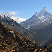Ama Dablam towers above the Khumbu Valley, Nepal, from near Namche Bazaar. Thyangboche Monastery is visible in the foreground, and the massive South Face of Lhotse and Nuptse rise in the distance. Everest is obscured by cloud