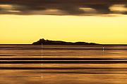 The island Svinøya, on the west coast of Norway, surrounded by golden sea during amazing sunset. Captured with 600mm and long shutter speed   Svinøya omgitt av gyllen sjø. Tatt med 600mm brennvidde, og lang lukketid under en fantastisk solnedgang.
