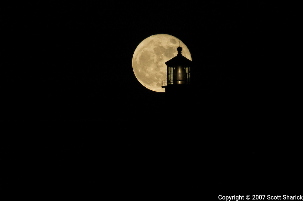 A view of the Makapuu Lighthouse silhouetted by a full moon.