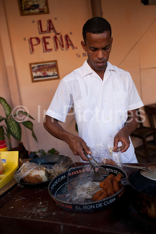 A Cuban man serves croquettes from a tray in a small local cafe, Havana old town.