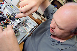 Man with disability using screwdriver to repair computer,