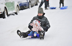 © Licensed to London News Pictures. 20 January 2013. Chipping Norton, Oxfordshire. Proud dad Ron Gallimore (35) with his twin daughters Hannah and Jessica (14 mths). Probably the best Street in England for sledging? Residents of The Leys in Chipping Norton have made a super sledging run in the road. The local children even prevented council workers from salting the road by sitting down across the road to block the gritters. Everyone who live in the Leys seems to love the sledging run and have even joked that they want to apply for a ski lift to be installed for future years fun.. Photo credit : MarkHemsworth/LNP