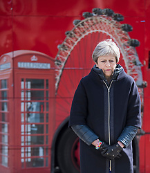 © Licensed to London News Pictures. 22/03/2018. London, UK. A London bus passes in the background as British Prime Minister THERESA MAY places a floral tribute at Parliament Square, outside the Houses of Parliament in Westminster, London on the one year anniversary of the Westminster Bridge Terror attack in which lone terrorist killed 5 people and injured several more, in an attack using a car and a knife. The attacker, 52-year-old Briton Khalid Masood, managed to gain entry to the grounds of the Houses of Parliament and killed police officer Keith Palmer. Photo credit: Ben Cawthra/LNP