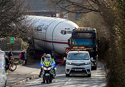 © Licensed to London News Pictures; 27/02/2021; Bristol, UK. A Boeing 727 fuselage is manoeuvred round tight corners on its way to the business Pytch in Brislington having been transported by road from Cotswold Airport to Bristol via the M5 and M4. Pytch owner Johnny Palmer will use the plane fuselage for an eco-friendly office and event space for the business. The plane as used by Japan Airlines before going into private ownership in the 1970s, sold for £50million when new. Mr Palmer got it for less than £100,000 because it does not have an engine or wings. Photo credit: Simon Chapman/LNP.