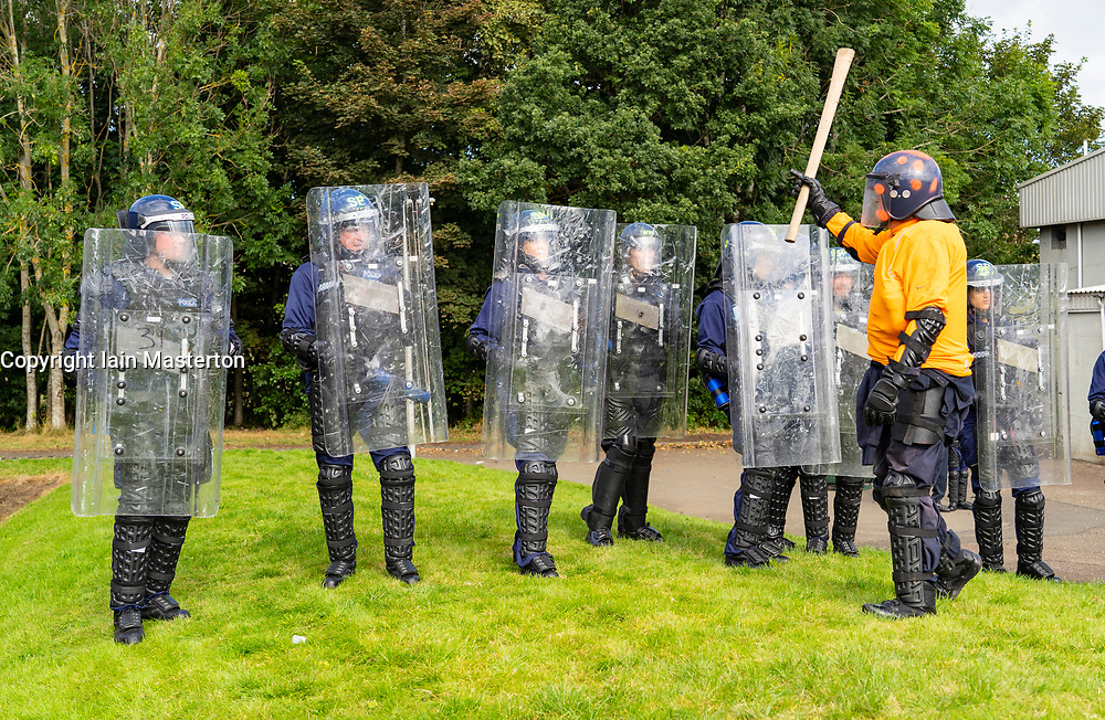 South Queensferry,, Scotland, UK. 16th September 2021. Police Scotland invite the press to witness their ongoing public order training at Craigiehall Camp at South Queensferry. The training is designed to prepare police for the upcoming COP26 event in Glasgow in November where protests are anticipated. Police in riot gear faced up  against police taking the role of protesters throwing missiles and attacking them with clubs. Pic; Police taking role of Protesters attack riot police during training.  Iain Masterton/Alamy Live News.