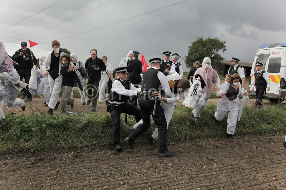 Climate activists from the Building Block, one of three grops of activists, are making their way across fields and passed police to join the ongoing blockade of Coryton oil refinery. The out numbered police manage to stop a few activists and confiscate some materials but fail to make any arrests. The activists are all peaceful and avoid arrest only by peaceful means, by out-running police and out number them.<br /> <br /> Crude Oil Awakening is a coalition of climate change activist groups. On Saturday Oct 16 they shut the only entrance to Coryton oil refinery in Essex, UK with the aim of highlighting the issues of climate change and the burning of fossil fuels. The blockade meant that a great number of trucks with oil were not able to leave the refinary during the day of action.