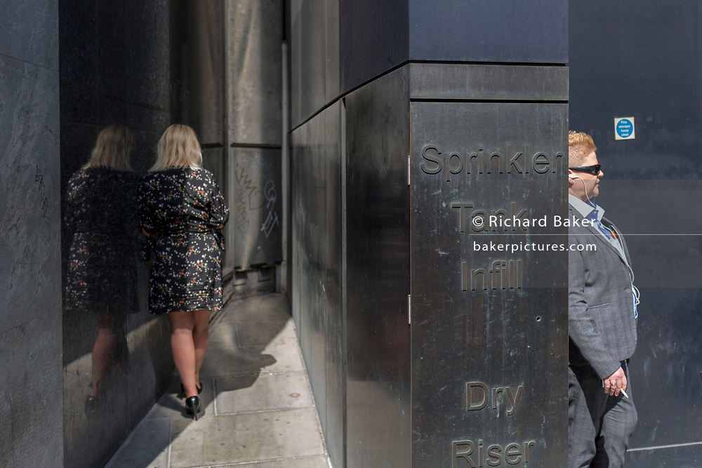 Wmokers enjoy summer sunshine in a quiet corner off Threadneedle Street in the City of London, the capital's financial district (aka the Square Mile), on 22nd August 2019, in London, England.